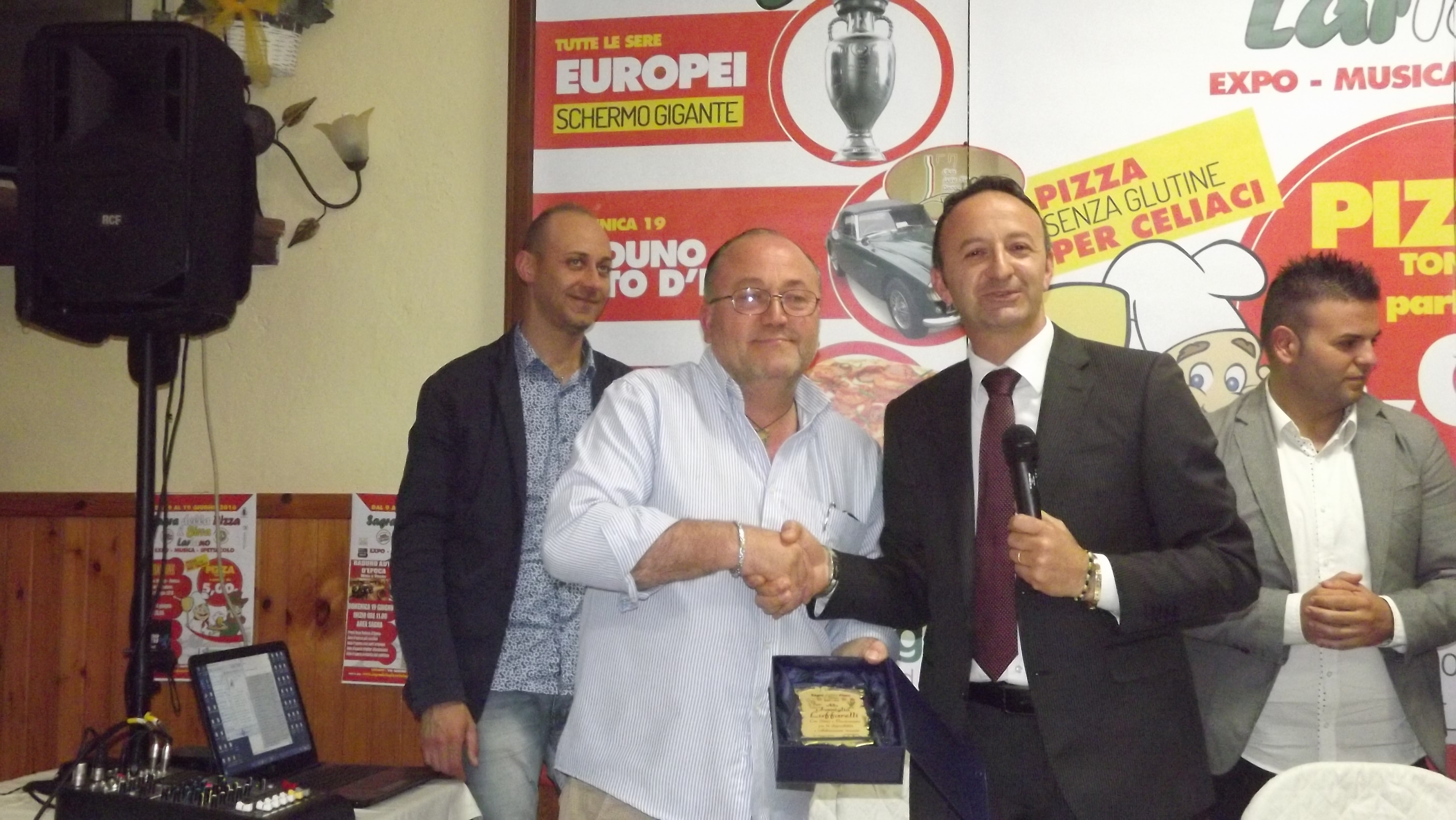 il presidente Paolo Anselmi consegna una targa a Mario Luffarelli
